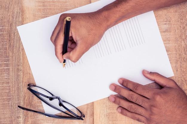 Bebouwde hand van zakenman die op papier bij lijst in bureau schrijven