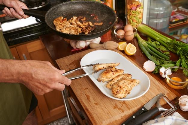 Bebouwde handen van anonieme kok die gebraden vlees met tang overbrengen