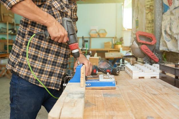 Bebouwde man boren houtwerk in een workshop