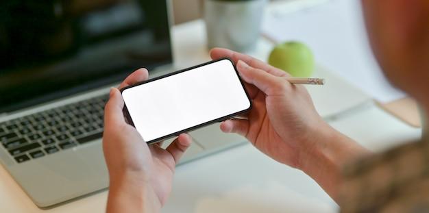 Bebouwde mening die van jonge zakenman horizontale smartphone houdt