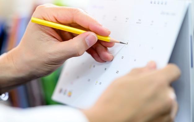 Bebouwde mening die van mensenhand geel potlood houden schrijvend op kalender.