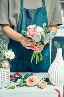 Bebouwde mening over creatieve bloemist die bloemboeket in bloemenstudio maken. jonge vrouw in werkkleding werkplek. bloemenwinkel, business, verkoop en bloemisterij concept. kopieer ruimte voor ontwerp