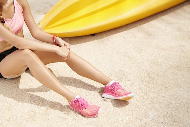 Bebouwde mening van vrouwelijke agent die roze loopschoenen dragen die rust op zand in openlucht hebben na actieve lichaamsbeweging. jonge sportvrouw in sportkleding ontspannen op het strand tijdens de ochtend training