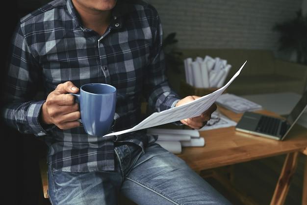 Bebouwde mens die blauwdruk controleert terwijl het hebben van thee
