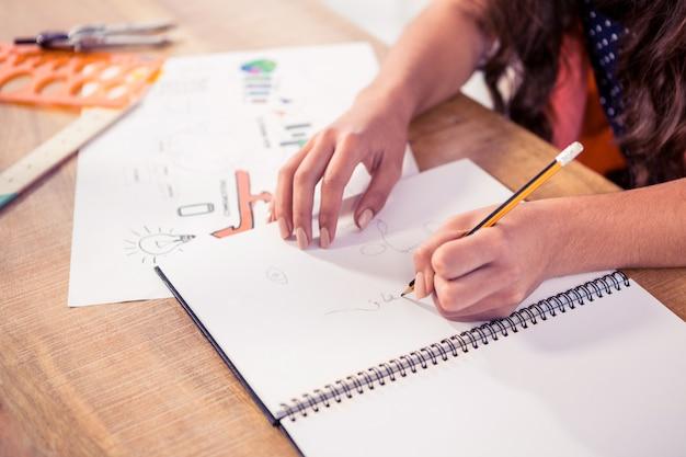 Bebouwde onderneemster die in boek op bureau op creatief kantoor schrijven