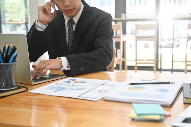 Bebouwde ontsproten zakenman die een telefoon roept en laptop computer op bureau met behulp van.