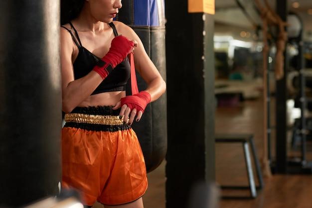 Bebouwde sportvrouw die voor het in dozen doen oefening in een gymnastiek voorbereidingen treffen