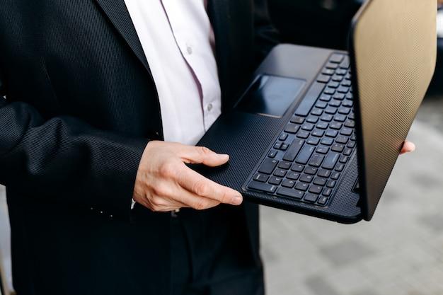 Bebouwend beeld van laptop van de zakenmanholding in zijn handen en close-up.