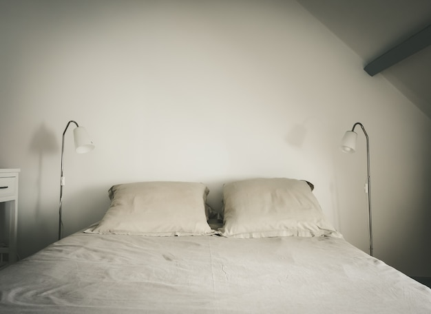 Bed en lamp in een witte slaapkamer. witte muur achtergrond