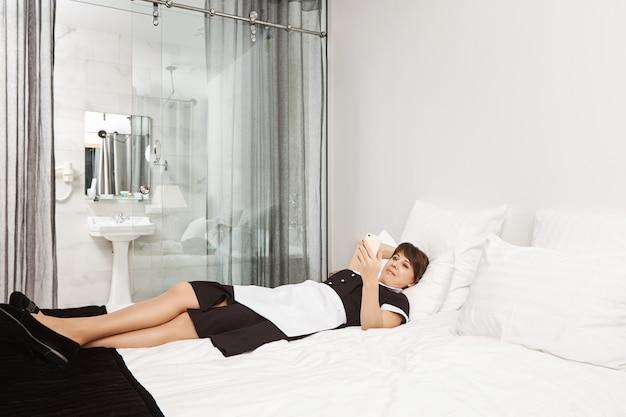 Bed is zo zacht en comfortabel. portret van dienstmeid die regels overtreedt en op slaapkamer in hotelkamer ligt, bladert of video's bekijkt met smartphone in plaats van het appartement van de klant schoon te maken