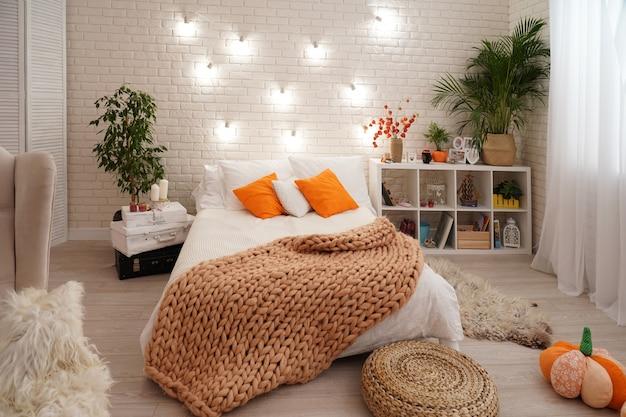 Bed met licht beddengoed bedekt met een gebreide deken van grof garen.