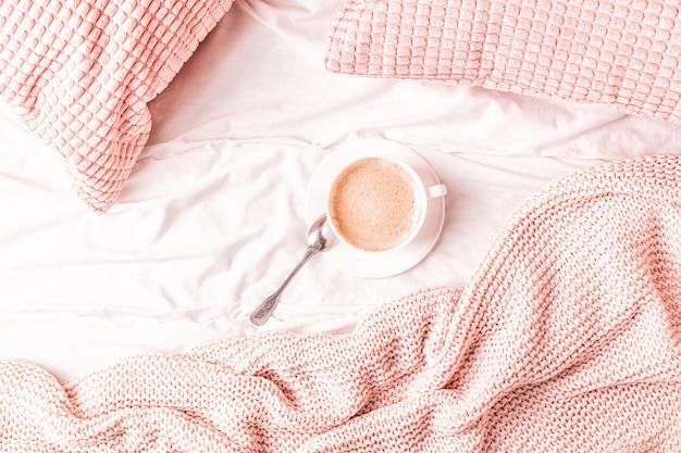 Bed met roze gebreide plaid en koffie, bovenaanzicht, kopie ruimte, plat leggen.
