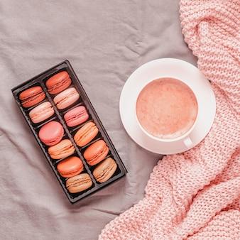 Bed met roze gebreide plaid, koffie en bitterkoekjes, bovenaanzicht, kopie ruimte, plat leggen.