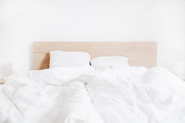 Bed met schoon wit linnengoed en witte muur