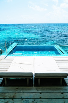 Bed zwembad en zwembad met zee achtergrond in maldiven