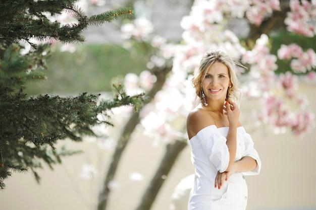 Bedacht blond in een witte jurk in het park