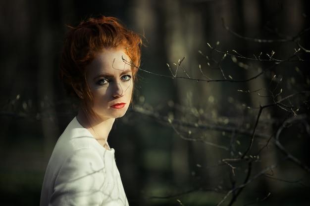 Bedacht roodharige meisje met rode lippen op zoek naar het frame