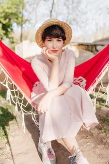 Bedachtzaam groenogig meisje in trendy schoenen chillen in een rode hangmat, moe na een lange reis met vrienden