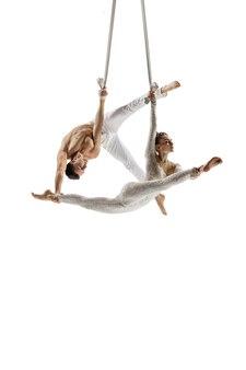 Bedachtzaam. paar acrobaten, circusatleten geïsoleerd op een witte studio achtergrond. training perfect gebalanceerd tijdens de vlucht, ritmische gymnastiekartiesten oefenen met apparatuur. genade in uitvoering.