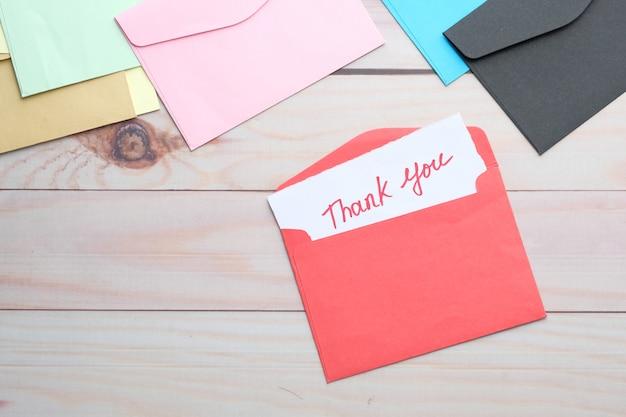 Bedankt bericht en envelop op houten tafel