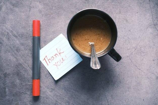 Bedankt bericht op plaknotitie en een koffiemok op tafel