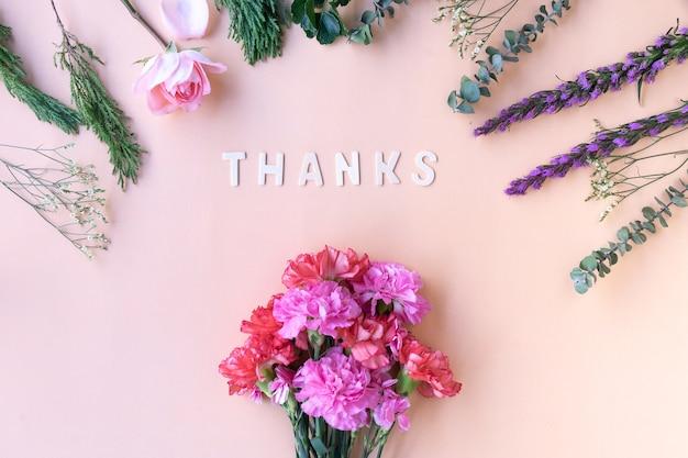 Bedankt houten woord met verse bloemen anjers op zachte room roze achtergrond