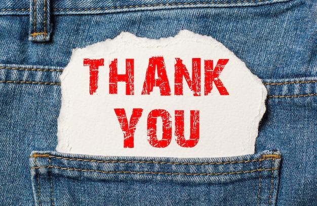 Bedankt op wit papier in de zak van blauwe spijkerbroek
