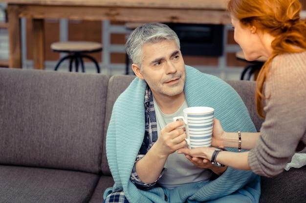 Bedankt schat. aangename zieke man die lacht terwijl hij een kopje thee uit de handen van zijn vrouw neemt
