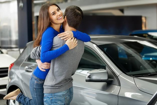 Bedankt schat! jonge mooie vrouw knuffelt haar vriendje, bedankt voor de nieuwe auto