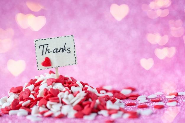 Bedankt tekst aan boord samengesteld in hoop rode en witte harten op glanzende roze bokeh muur voor valentijnsdag en bedankje dag concept.