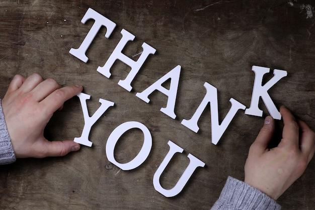 Bedankt woord van witte houten letters op tafel en handen