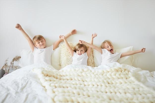 Beddengoed, slaap, rust en ontspanning concept. binnenopname van drie kinderen die zich slaperig voelen terwijl ze 's ochtends vroeg voor school wakker worden. twee broers en zus geeuwen en die zich uitstrekt in bed