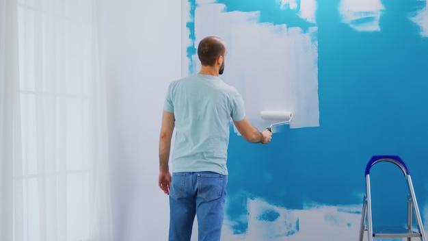 Bedekkende muur blauwe verf met witte verf met behulp van rolborstel. klusjesman aan het renoveren. appartement herinrichting en woningbouw tijdens renovatie en verbetering. reparatie en decoreren.