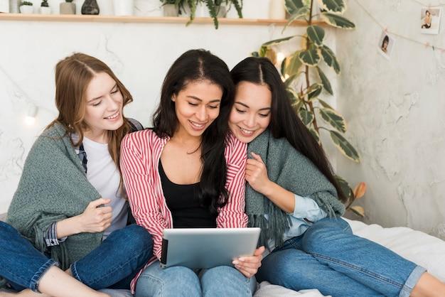 Bedekt met deken meisjes zitten en kijken naar tablet pc-scherm