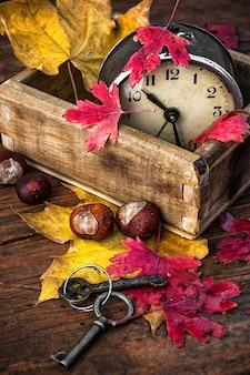 Bedekt met herfstbladeren oude wekker in houten kist op de tafel