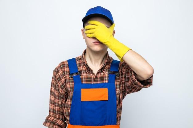 Bedekte ogen met hand jonge schoonmaakster die uniform en pet met handschoenen draagt
