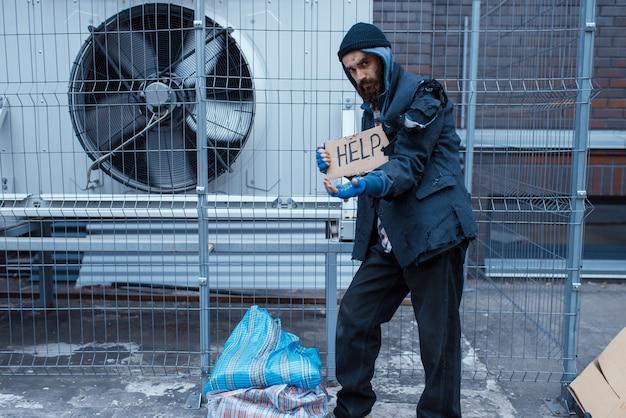 Bedelaar man en help ondertekenen op straat in de stad