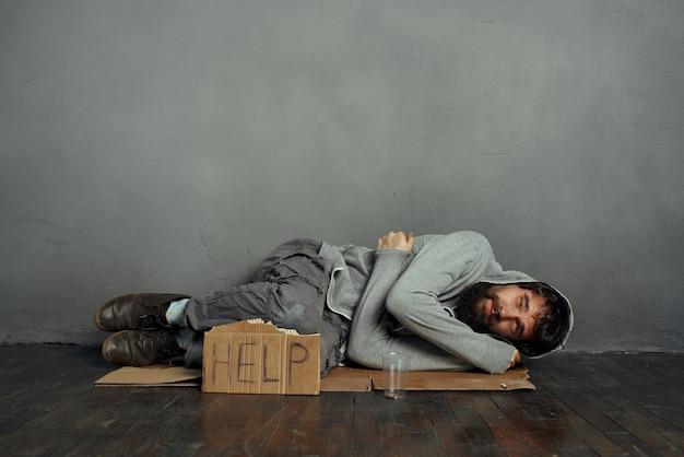 Bedelaar man liggend op de vloer dakloze depressie helpt geldproblemen