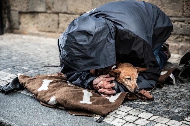 Bedelaar met hond die om een aalmoes bedelt, europese stad