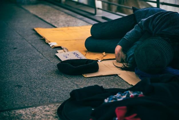 Bedelaars, dakloze mensen die op de vloer op een viaduct liggen.
