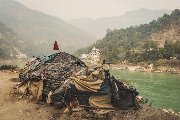 Bedelaarshut aan de rivier de ganges rishikesh op de achtergrond van een grote dure tempel. lagere kaste. sociale ongelijkheid. het probleem van armoede en het kastenstelsel van india