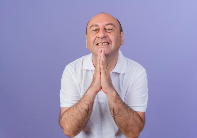 Bedelen casual volwassen zakenman handen samenstellen kijken camera geïsoleerd op paarse achtergrond met kopie ruimte