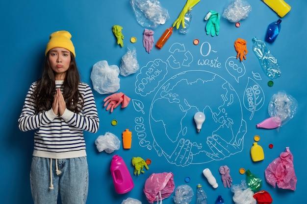 Bedelende trieste vrouw houdt de handpalmen tegen elkaar gedrukt, vraagt om de omgeving waarin we leven niet te vervuilen, gekleed in vrijetijdskleding