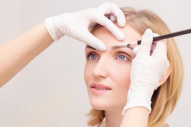 Bedenken. schoonheidsspecialiste handen doen wenkbrauw tatoeage op vrouw gezicht. permanente wenkbrauw make-up in schoonheidssalon.