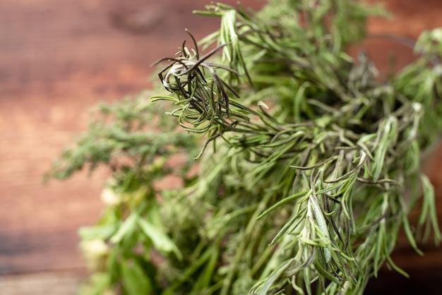 Bederfelijke, vervagende, drogende greens dille peterselie op een houten ondergrond.