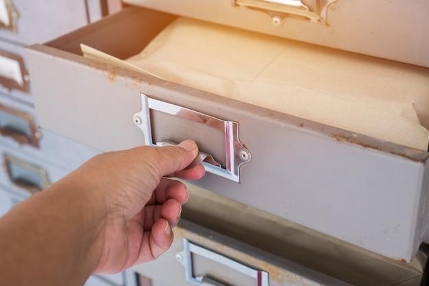 Bediende trekt een stapel oude ijzeren kast of kast met kastjes in de kleedkamer voor de middelbare school