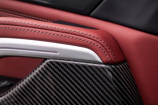 Bedieningspaneel met chromen handgreep op de autodeur, gebruikelijk zwart en rood echt leer in een nieuwe auto. armsteun in luxeauto