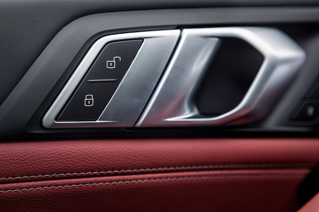 Bedieningspaneel met chromen handgreep op de autodeur, gebruikelijk zwart en rood echt leer in een nieuwe auto. armsteun met bedieningsknoppen