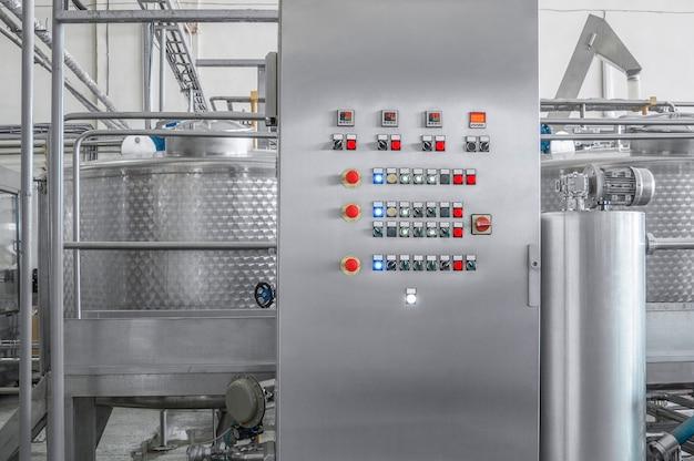 Bedieningspaneel met knoppen en een tank bij een drankenfabriek productie van flessen en drank