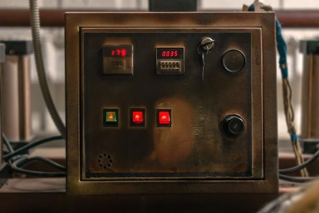 Bedieningspaneel van een oude industriële hittepers verduisterd door de tijd en hoge temperaturen